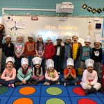 Kindergarten class picture with students in chef hats and mustaches