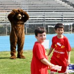 Two students smiling with a bear mascot in the background