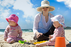 Photo of a woman and her children wearing hats and long sleeved shirts.