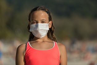 a young girl in a swimsuit wearing a mask on a beach