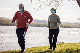 two walkers outside by lake wearing cloth face masks