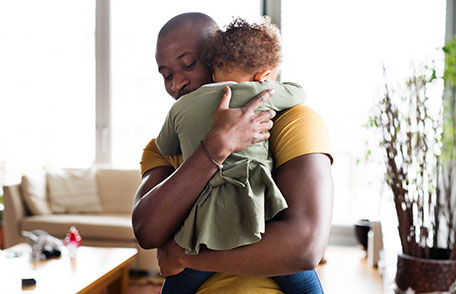 Father hugging child and smiling