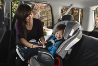 Woman buckling her child into carseat