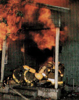 Bomberos usando aparatos de respiración autónomos (SCBAs, por sus siglas en inglés) y otros equipos de protección en el lugar de un incendio.