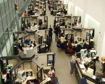Centro de despacho de llamadas 911 del Departamento de Policía de Nueva York que cuenta con un diseño en un área abierta en el cual las personas laboran muy cerca de las otras.