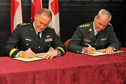 General Walt Natynczyk, Canada's Chief of the Defence Staff (left), and General Knud Bartels, Chief of Defence of Denmark, sign a Memorandum of Understanding on military cooperation in the Arctic.