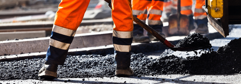 Road construction, worker with shovel