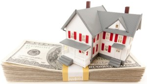 Small House on Stack of Hundred Dollar Bills Isolated on a White Background.