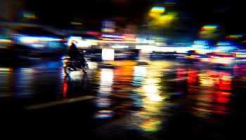 Le mouvement urbain et ses reflets lumineux sous la pluie