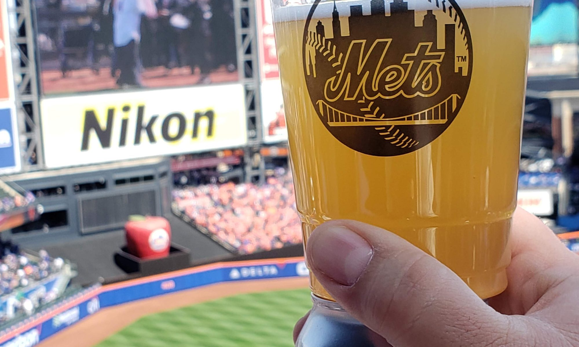 holding a NEIPA session ale in a Mets plastic cup at citi field up to the scoreboard with the field in the background