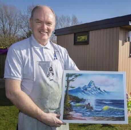 Painter David Wiles holding one of his paintings
