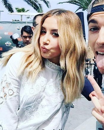 Ashley Tisdale wearing a H&M Lace Blouse while posing with a fan.