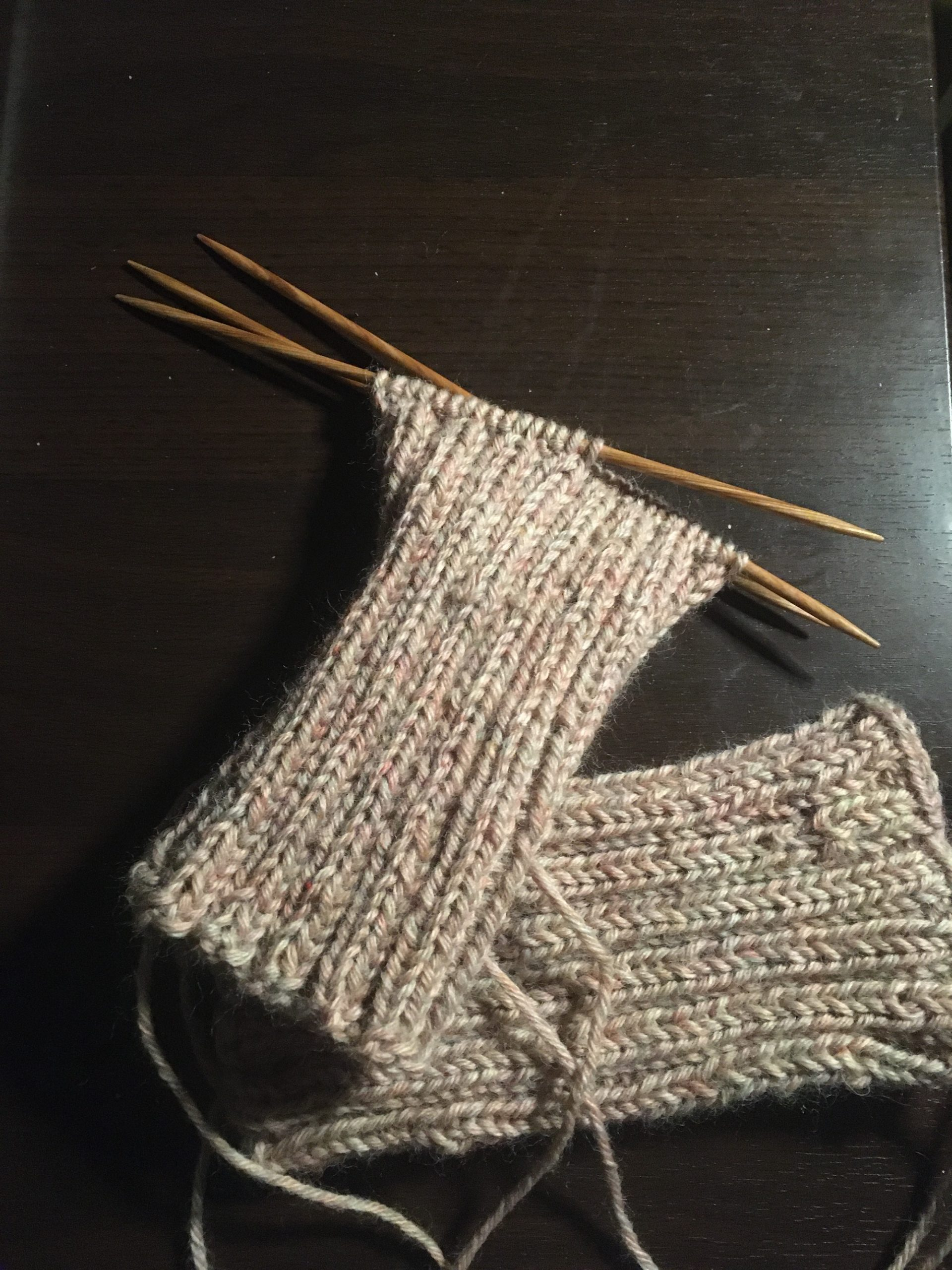 A pair of knit wristers (one done, one in progress and on the needles) in a pale khaki yarn.
