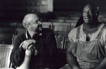 black and white photo of director Frank Darabont talking to actor Michael Clarke Duncan on the set of The Green Mile