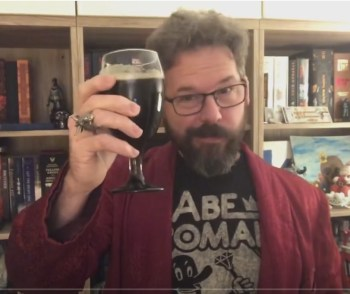 photo of Jeff Terry wearing a red jacket and holding a glass of beer