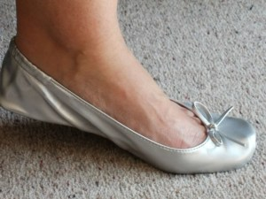Pie-de-mujer-con-una-zapatilla-estilo-bailarina-de-color-plateado
