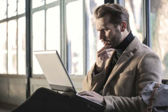 Smartly dressed man reads laptop