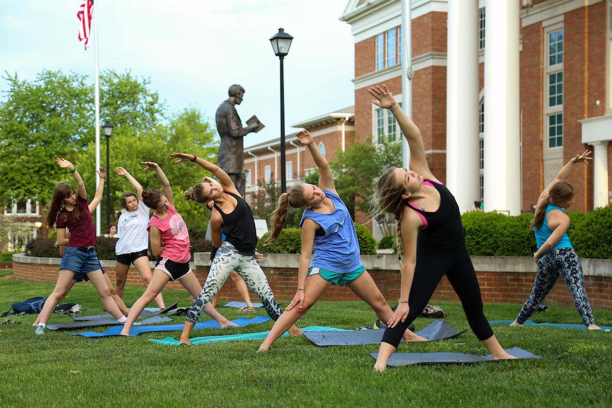 students doing yoga in front of Crounse Hall