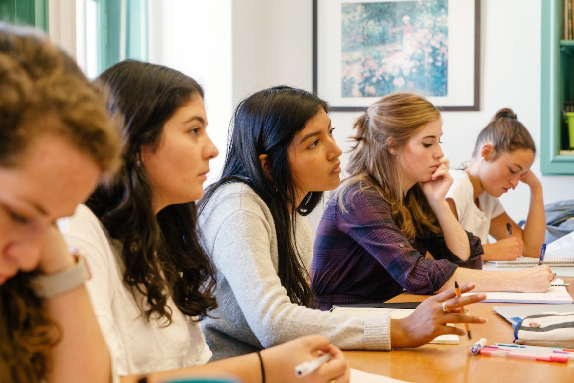female South American student listens in class
