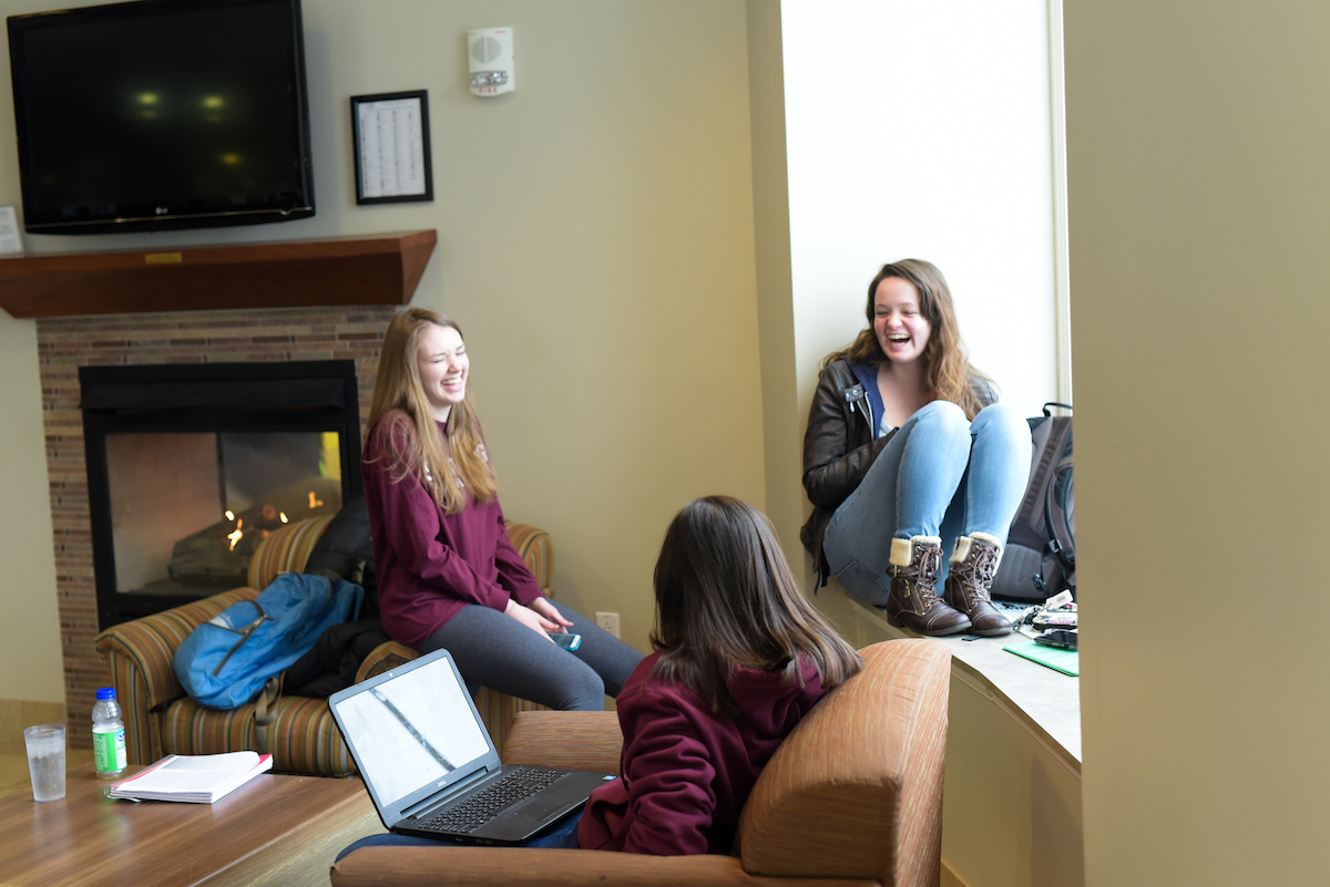 females students laughing inside the Campus Center