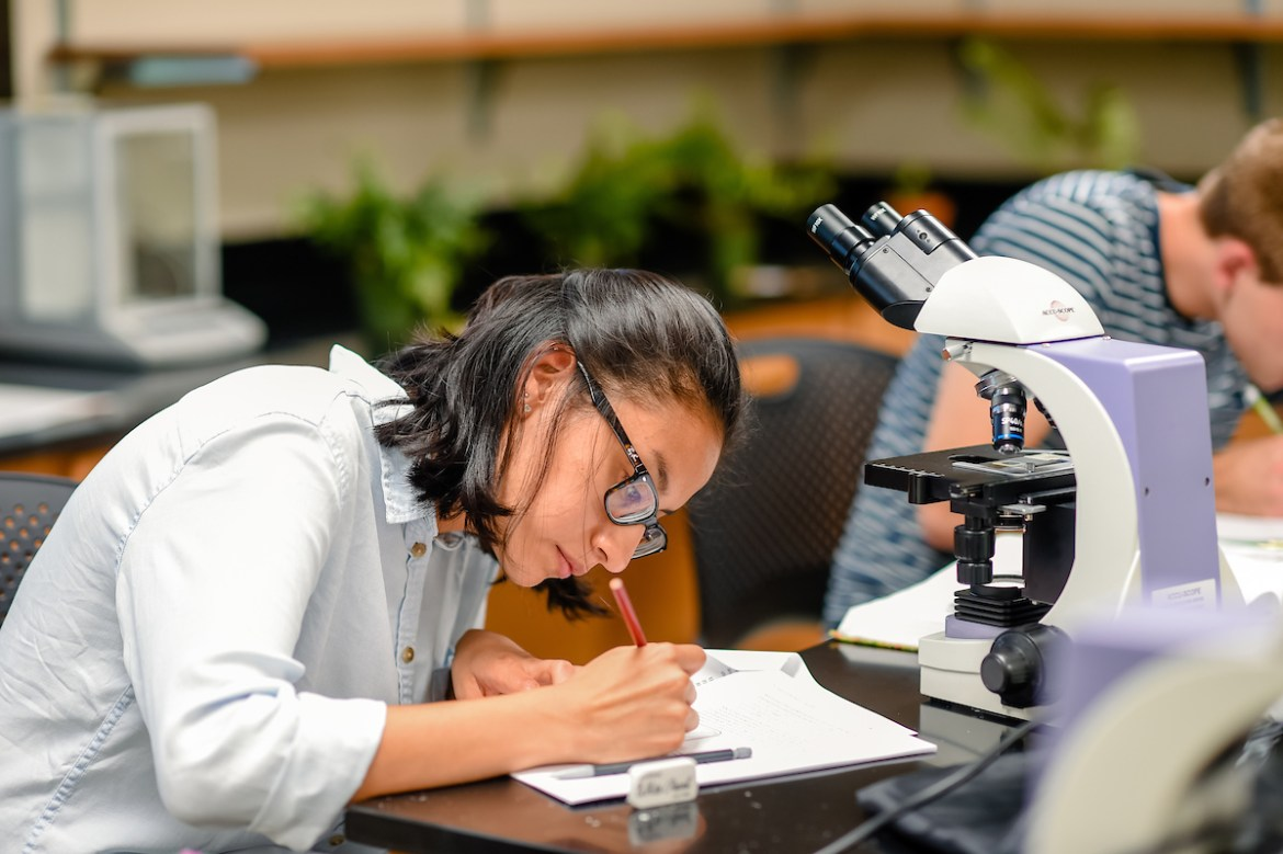 female student taking notes in front of a microscope
