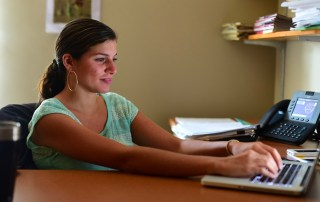 Dr. Dina Badie sits before a laptop in her Centre College office