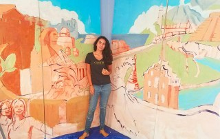 Isabelle Ballard '16 stands before a mural depicting Centre's study abroad experience
