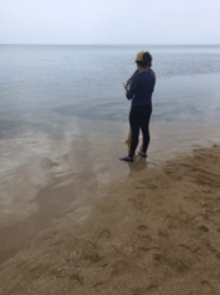 person standing on the beach, looking out on the water