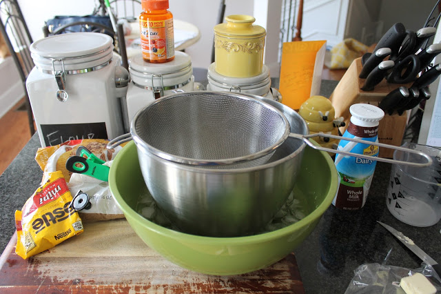 Metal mixing bowl inside of larger bowl of ice, with a mesh strainer on top of the metal bowl