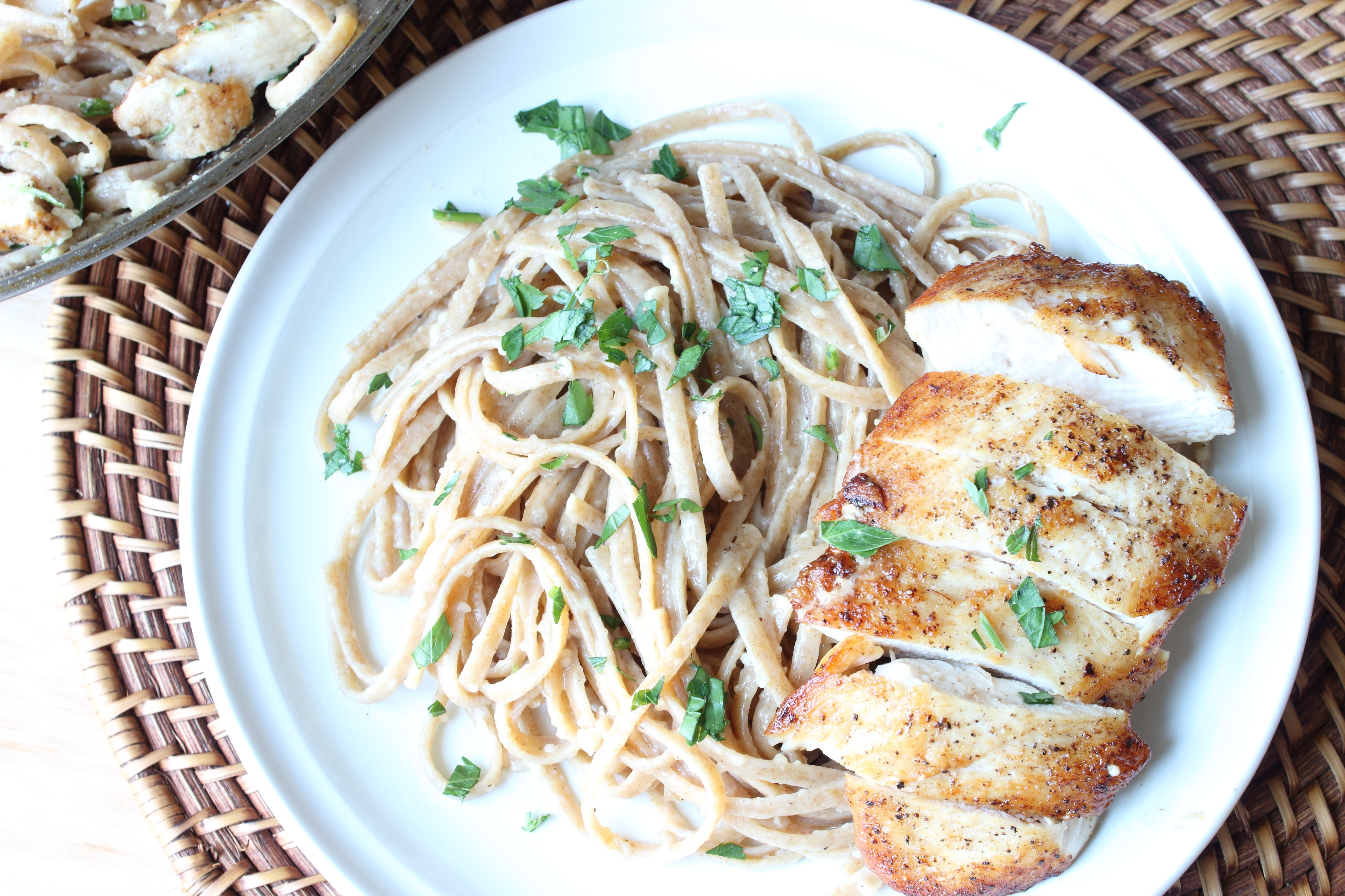 Pasta on a plate with wine sauce and a sliced chicken breast