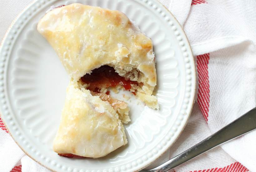 a cherry handpie on a plate that is cut in half