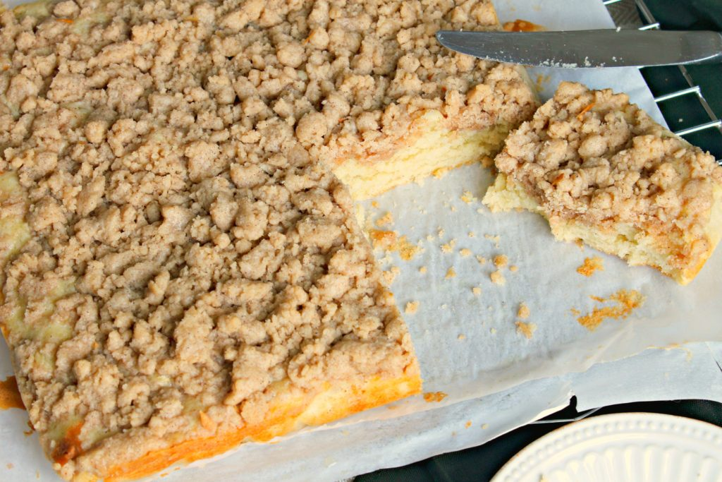 Classic crumb cake being cut with a knife