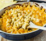 zoomed in shot of Creamy Baked Mac & Cheese scooped onto a wooden spoon
