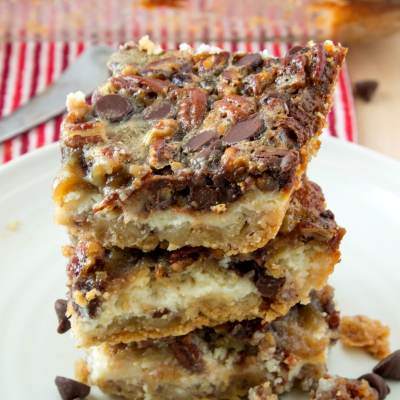 styled shot of a stack of chocolate pecan pie cheesecake bars