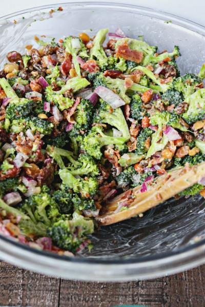 shot of fresh broccoli salad with crispy bacon in a bowl with a wooden spoon