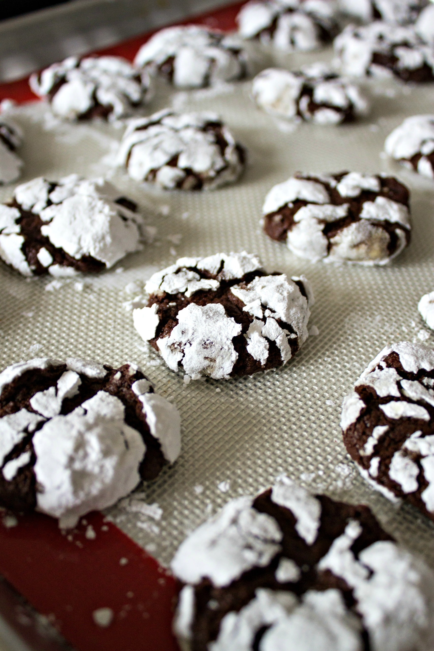 chocolate espresso snowcap cookies on a cooling mat on a cookie sheet