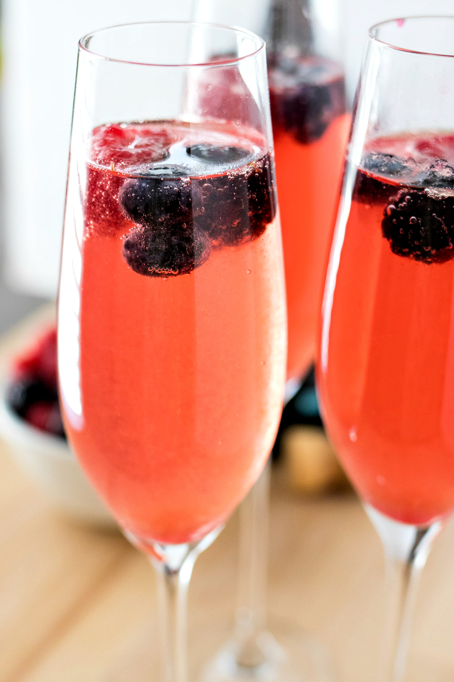 Berry Mimosas - A refreshing and simple mimosa made with mixed berry simple syrup and prosecco or champagne. Garnish with a few berries and you've got yourself the perfect drink for summer!