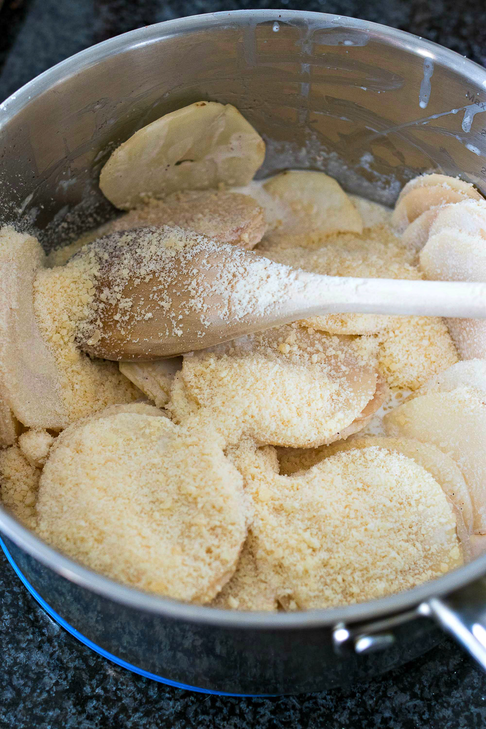 Mixing the potato slices with the dry ingredients