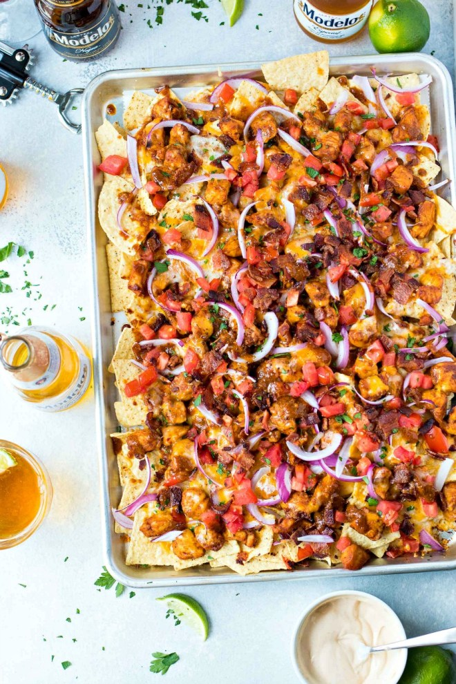 BBQ Chicken Nachos - Made with tortilla chips topped with BBQ chicken, Monterrey Jack and cheddar cheeses, fresh tomatoes, sliced red onion, and crispy bacon, these nachos are a fun and easy party snack that is perfect for a crowd!