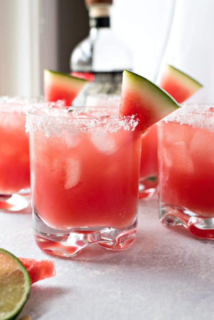styled shot of glasses of Watermelon Margaritas with ice cubes and slices of watermelon and lime around them with a bottle of rum