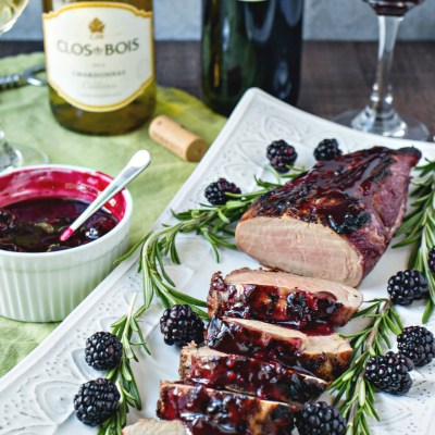 styled shot of Blackberry & Rosemary Pork Tenderloin on a platter with blackberries sprigs of thyme a bowl of blackberry sauce two bottles of wine and full wine glasses on a cloth napkin, shot from the front