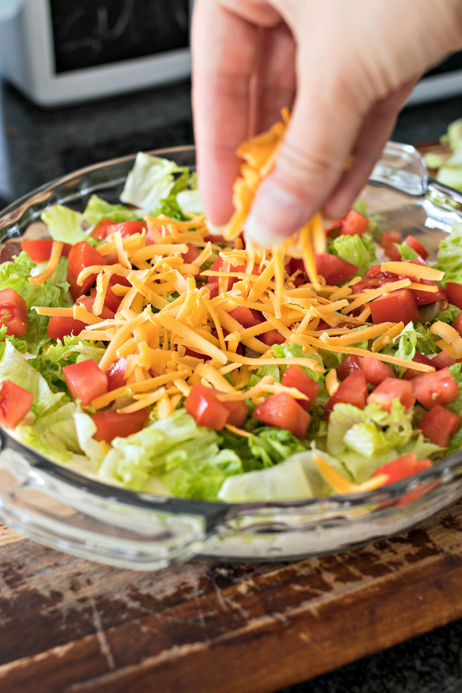 Adding shredded cheese on top of lettuce and tomatoes