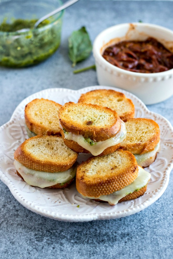 Mini Pesto Grilled Cheese - Fresh basil pesto and sliced provolone cheese are sandwiched into a crusty baguette and grilled to perfection to make the best appetizer for any event. Don't forget to serve with homemade garlic butter tomato sauce for dunking!