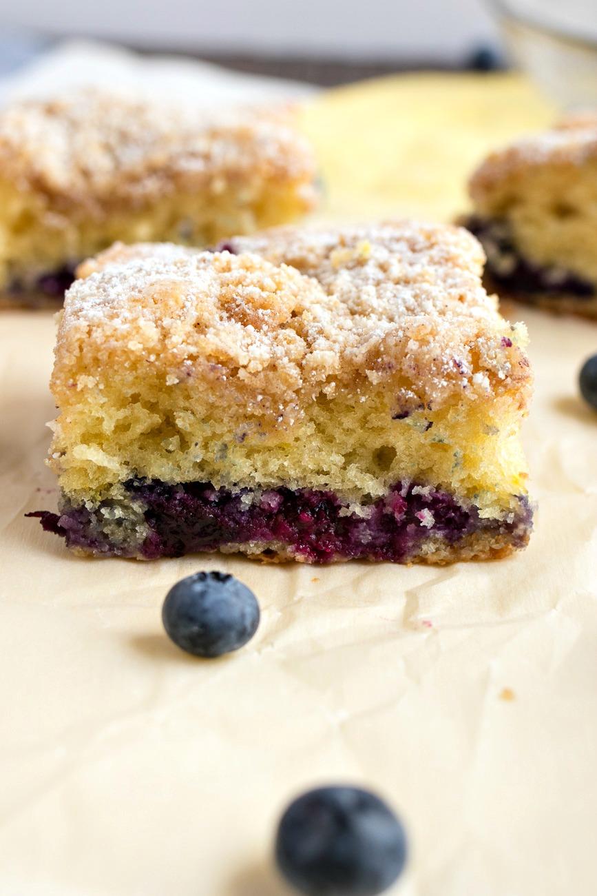 Blueberry Coffee Cake piece surrounded by blueberries