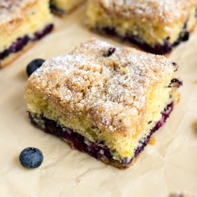 slices of blueberry coffee cake on top of parchment paper with blueberries around it, shot from a side angle