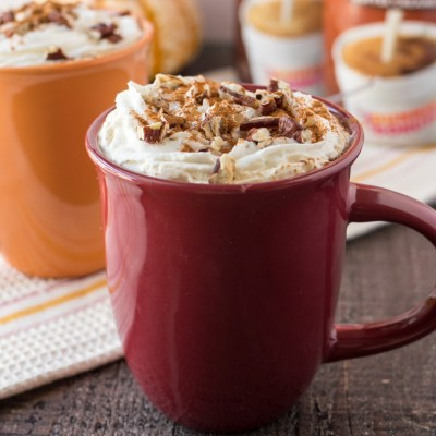two mugs of Cinnamon Maple Latte topped with whipped cream and sprinkled with pecans with dunkin donuts creamer and a stack of pumpkins on top of a cloth napkin, shot from a side angle