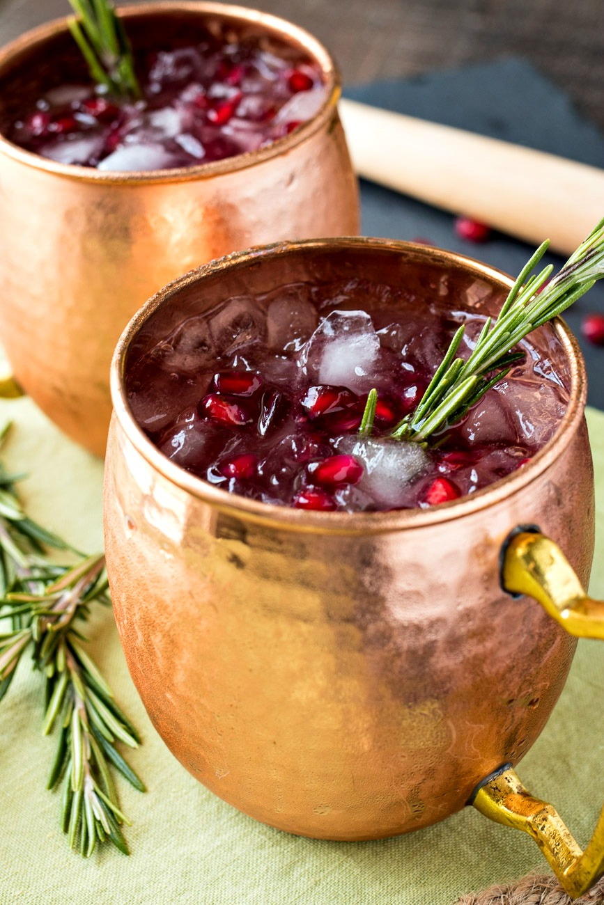 Pomegranate Rosemary Moscow Mule in a copper mug with a sprig of rosemary