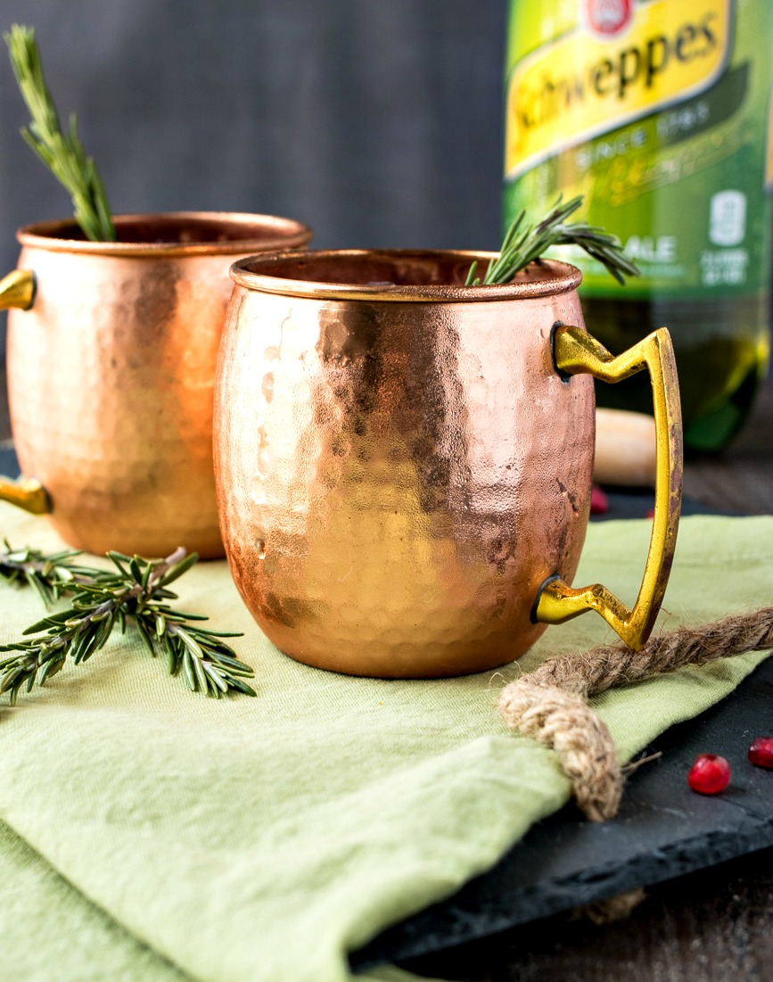 Two copper mugs of Pomegranate Rosemary Moscow Mule
