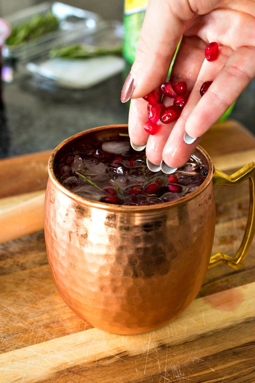 Adding pomegranate pieces to the mug