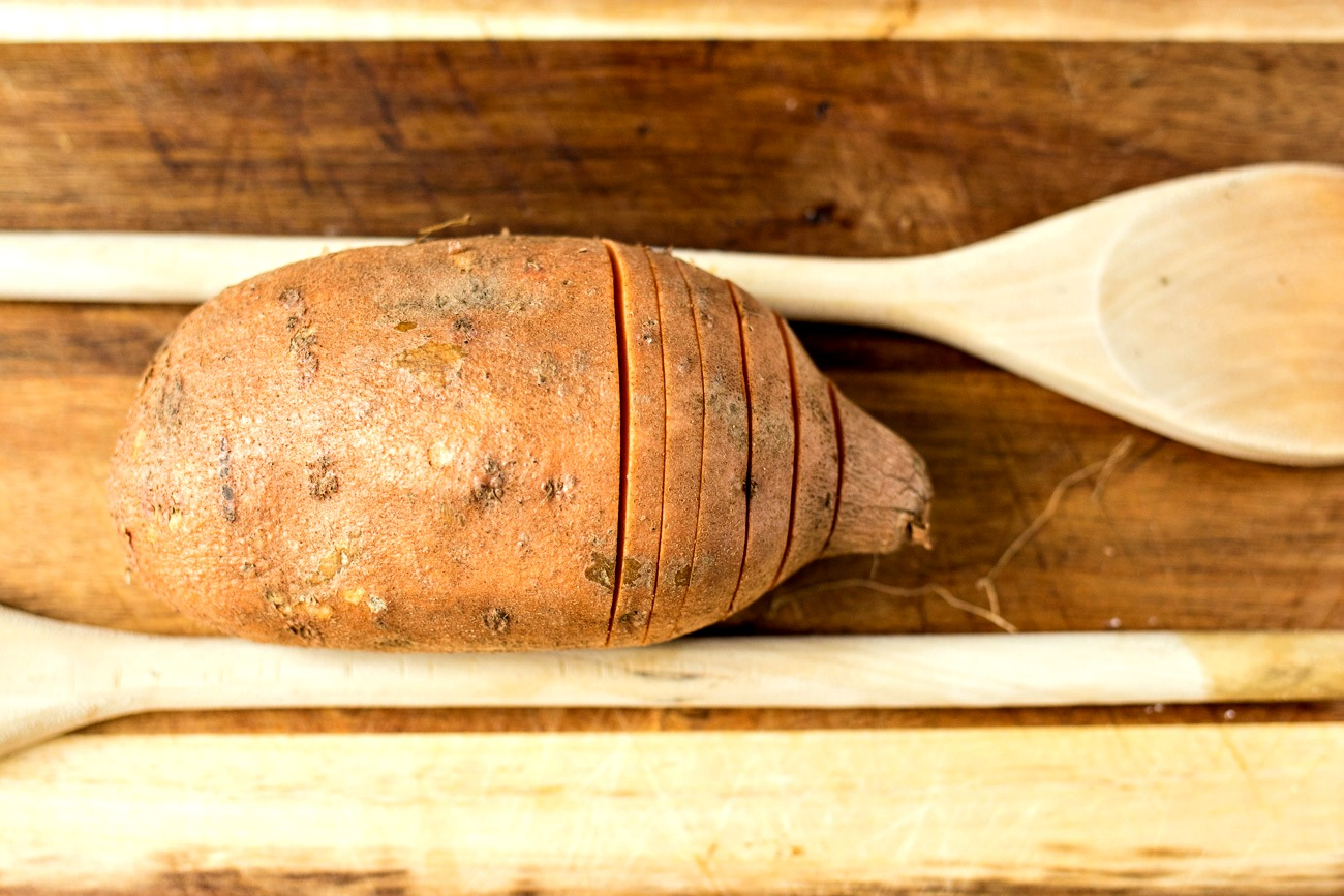 Hasselbeck sliced potato next to a wooden spoon